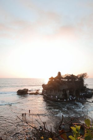 Have you ever wondered whether you should visit Tanah Lot Temple? It is one of the top attractions in Bali Indonesia and one of the most stunning sunsets in all of Asia! The temple is a top bucket list attraction to add to your list of things to do in Bali- and a perfect thing for all travellers- here's why! #bali #tanahlot #thingstodo
