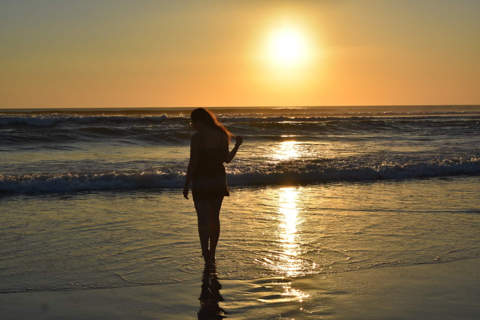 Solo female traveller admiring a stunning golden sunset at the beach in Bali, Indonesia.