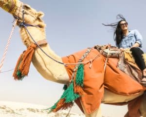 Sitting on a camel in the desert of Qatar