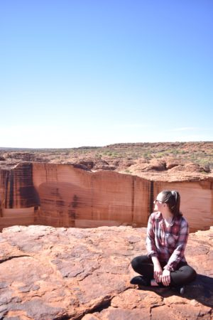 Sitting at the edge of Kings Canyon, with blue skies and outback Australia colours all around.